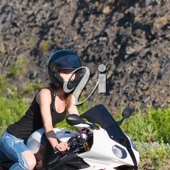 Young beautiful blonde girl in trendy blue jeans and a black T-shirt on the nature behind the wheel of modern motorcycle. Portrait in soft sunny colors.