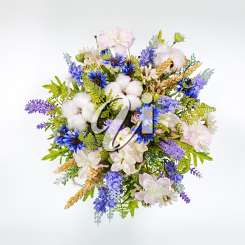 Table floral arrangement made of artificial flowers on white background. Flat lay, top view..