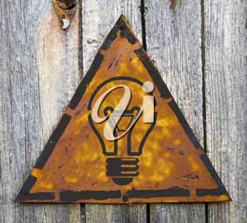 Royalty Free Photo of a Light Bulb on a Rusty Sign on a Wooden Wall