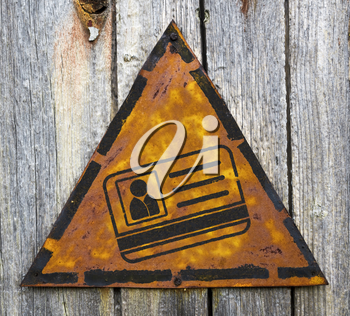 Royalty Free Photo of an ID on a Rusty Sign Against a Wooden Wall