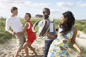 Group Of Young People Having Fun Dancing On Beach Together