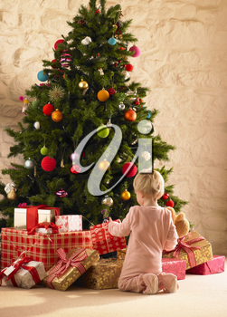 Little girl with parcels round Christmas tree