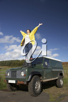 Young woman in countryside with SUV