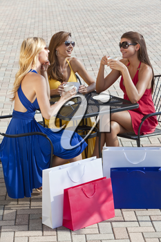 Three beautiful and sophisticated young women friends wearing sunglasses and having coffee around a modern city cafe table surrounded by shopping bags