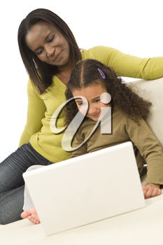 A beautiful young African American mother and her mixed race young daughter using a laptop at home on a settee