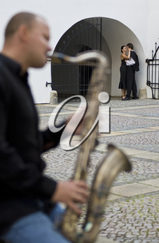 Selective focus shot of a street musician playing his saxophone while a romantic couple kiss in the background