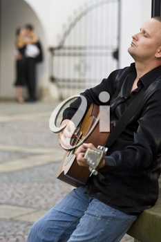A street musician playing his guitar serenades a romantic couple kissing out of focus in the background