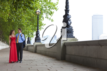 Romantic man and woman couple holding hands walking by the River Thames in London, England, Great Britain