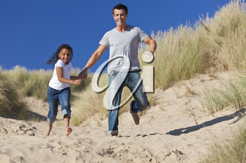 A man and young girl, father and mixed race daughter, running and having fun in the sand dunes of a sunny beach