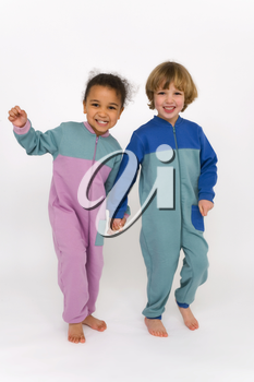 A beautiful mixed race little girl and a cute blonde boy dressed in sleep suits holding hands, laughing and having fun together