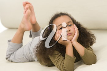 A beautiful young mixed race girl laying down on a settee