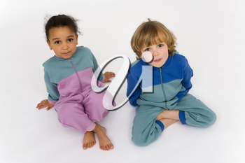 A beautiful mixed race little girl and a blonde boy dressed in sleep suits look up into the camera