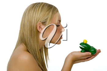 A gorgeous young blond woman kissing a toy frog