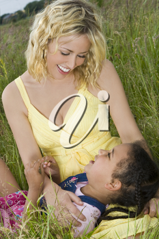 A beautiful blond haired blue eyed young woman having fun with a mixed race little girl in a field of long grass