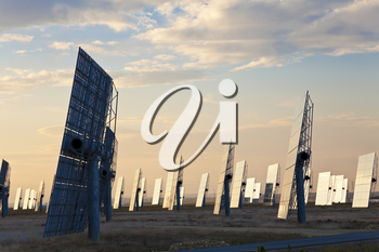 A field of solar mirror panels harnessing the sun's rays to provide alternative green energy at sunrise or sunset