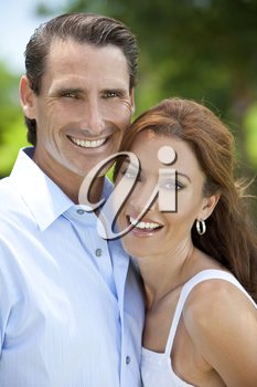 Portrait shot of an attractive, successful and happy middle aged man and woman couple in their thirties, together outside and smiling.