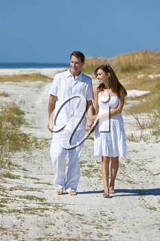 Man and woman romantic couple in white clothes holding hands and walking on a deserted tropical beach with bright clear blue sky