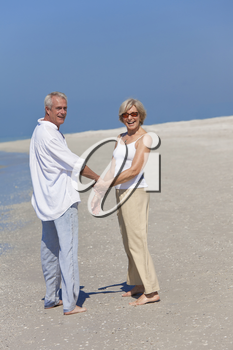 Happy senior man and woman couple together holding hands and walking on a deserted tropical beach with bright clear blue sky