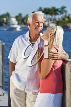 Happy senior man and woman couple together on vacation by the sea in a tropical setting with bright clear blue sky.