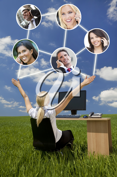 Business or social network connections concept photograph of woman businesswoman sitting at a desk using a computer in a green field raising her arms into a bright blue sky with fluffy white clouds