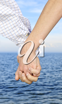 Mature romantic couple holding hands on the beach