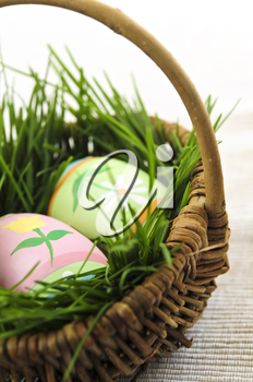 Easter eggs arrangement with green grass in a basket