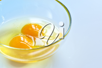 Raw eggs in a glass bowl close up