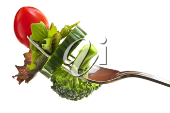 Fresh vegetables on a fork isolated on white background