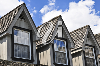 Window dormers on a house with wooden shingles on blue sky background
