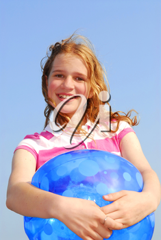Portrait of a young beautiful girl on sea shore with beach ball