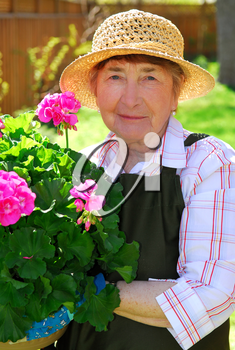 Senior woman holding a pot with flowers in her garden