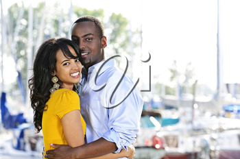 Young romantic couple hugging and standing at harbor