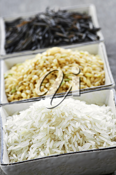 Three bowls of white, brown and wild black uncooked rice