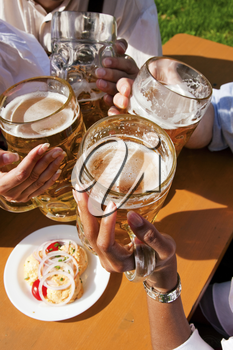 Group of four people in Couple in traditional Bavarian dress, Lederhosen and Dirndl (only parts of body to be seen), in a beer garden or at a festival like the Oktoberfest; focus on beer steins