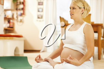 Pregnant woman meditating doing pregnancy yoga sitting on the floor in her home