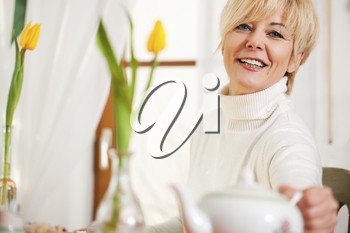 Woman sitting on a table for coffee or tea time grabbing for the coffee or tea pot, there are yellow tulip flower on the table, in the background is a window, whole scene is sunlit