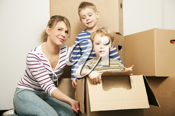 Family moving in their new house. The sons are sitting inside the moving boxes, everybody is looking rather cheerful