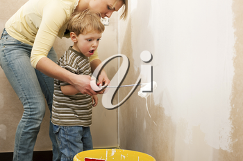Family - mother with son - painting the wall of their new home or apartment, apparently they just moved i