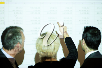 Group of people in front of a spreadsheet projected on wall (people only illuminated by projector, there are wirelines from projection on people and screen, selective focus on hand of presenter!)