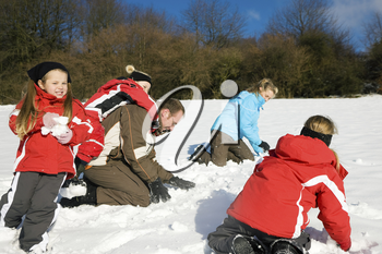 Family with kids having a snowball fight in winter on top of a hill in the snow