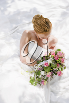 Bride sitting holding a bouquet of flowers in her hand