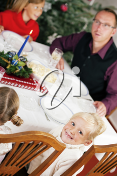 Family eating a traditional Christmas Dinner in front of the Christmas tree