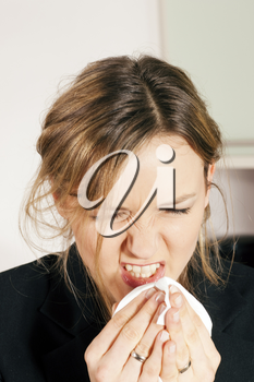 Woman with a flu or an allergy sneezing into her handkerchief