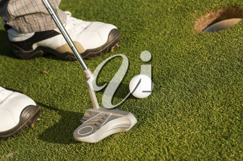 Golf player attempting to put the ball in the hole, closeup on golf club, hole and feet of man
