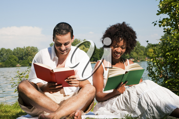 Couple reading books in the sunshine sitting at lake in summer