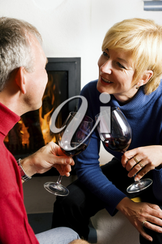 Mature couple having fun clinking glasses with red wine in a romantic setting
