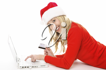 Shopping online is easy, convenient and secure.  Smiling female using a laptop and holding a credit card or other card to buy Christmas gifts, pay bills or  banking.  All data on back of card has been