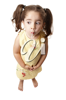 A small cute girl with hair in ponytails is sucking on a lollipop sweet.   She is standing on a white background and looking sideways.  Space for copy.