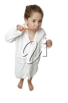 A young girl holding an orange toothbrush and brushing her teeth.