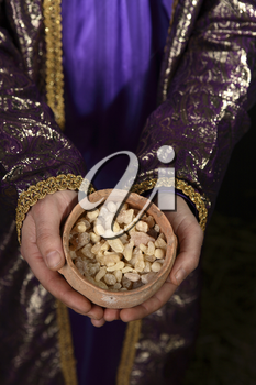 Wise man arrayed in purple cloak embrodered with metallic gold thread, his hands holding an ancient clay pot filled with the best hojari frankincense resin tears from dhofar region of Oman.  The aroma